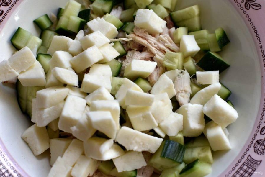Огурцы и сыр нарежьте среднего размера кубиками. Сложите все в миску.