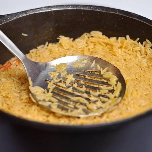 Добавьте чесночную головку обратно. Когда рис начнет поглощать воду снова уберите чеснок. Накрыть плов крышкой и готовить в течении 8 минут. Проверяйте каждые несколько минут, не впиталась ли вся жидкость, чтобы избежать пригорания.