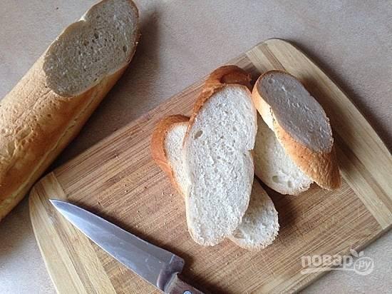 В идеале брускетту готовят из чиабатты, но можно за основу взять любой белый хлеб. Нарезаем его ломтиками толщиной чуть больше 1 см.