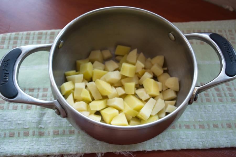 Нарезаем картофель кубиками, кладем его в кастрюлю. Заливаем водой. Варим до готовности.