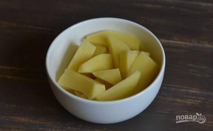 Картофель очистите и вымойте под проточной водой. Обсушите клубни и нарежьте их на небольшие дольки.