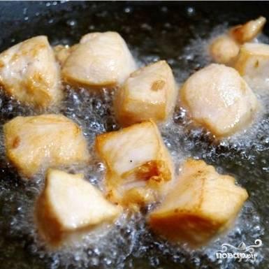 В воке разогреваем масло. В раскаленном масле небольшими порциями (чтобы кусочки именно обжаривались, а не тушились) обжариваем кусочки курицы - буквально по 1 минуте с каждой стороны. Небольшими порциями обжариваем все имеющееся мясо.