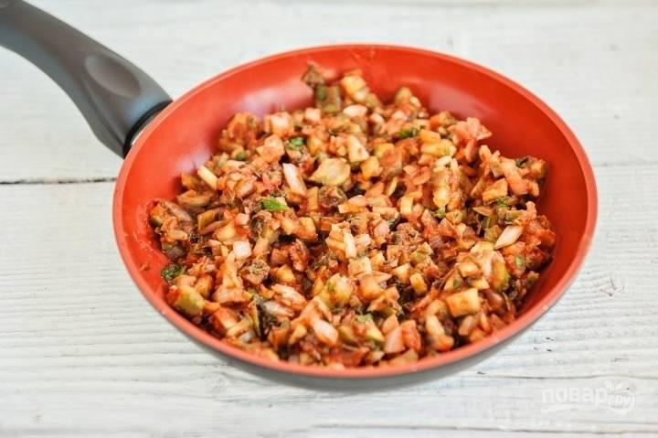 Мелко нарежьте огурцы, лук и петрушку. Тушите ингредиенты с маслом в томатной пасте в течение 10 минут.