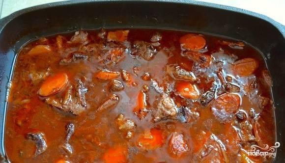 4.Не снимая с огня, добавьте в блюдо горячий мясной бульон. Влейте красное вино. Обратите внимание, что чем выше качество вина, тем более вкусное получится в итоге блюдо. Положите к мясу лавровый листочек. Добавьте томат и измельченный чеснок. Аккуратно все перемешайте.