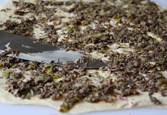 4. Сверху накройте вторым листом, на который нужно равномерно распределить уже остывшую начинку. Зелень вымойте, обсушите как следует и измельчите. Соедините с оставшимся сыром, намажьте полученной массой третий лист лаваша, выложенный поверх грибов.