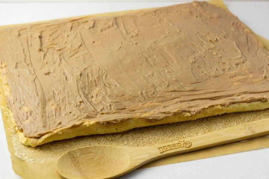 Разверните бисквит и смажьте кремом от края до края, затем снова сверните в рулет. Чуть меньше половины крема должно остаться для покрытия рулета сверху.