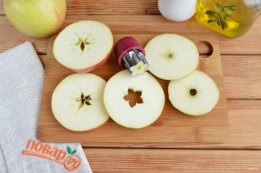 """Порежьте яблоки кружочками толщиной примерно 5-6 мм. Вырубкой для печенья """"звездочка"""" сделайте в центре каждого кружочка отверстие."""