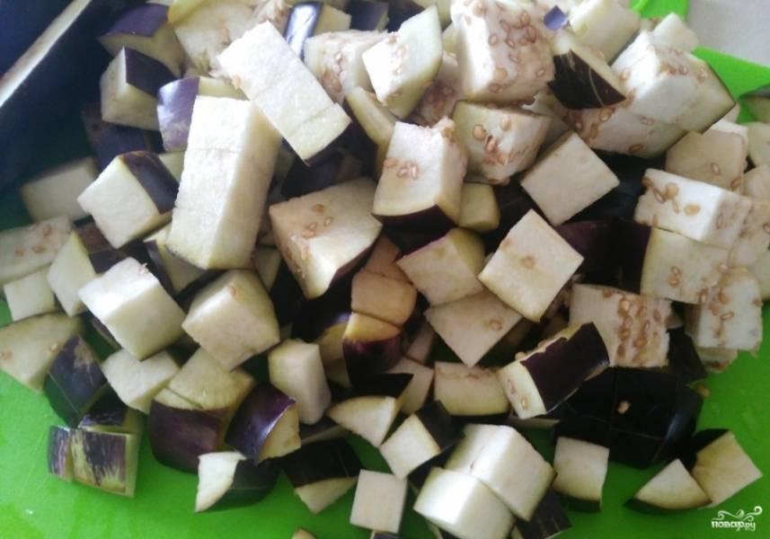 1.Баклажаны хорошенько моем, удаляем хвостики и разрезаем каждый на небольшие кубики. Перекладываем в кастрюлю и заливаем теплой водой, кладем столовую ложку соли и оставляем на 30 минут, чтобы ушла горечь.