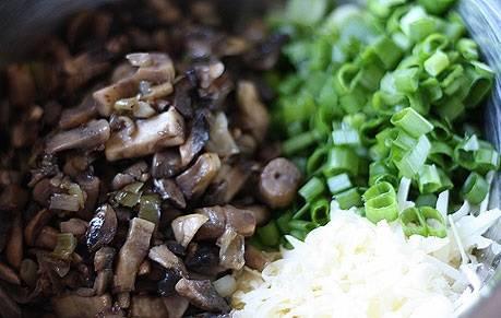 Измельчите на терке пармезан. Зеленый лук мелко порежьте. Затем смешайте лук, сыр и поджаренные грибы в одной емкости.