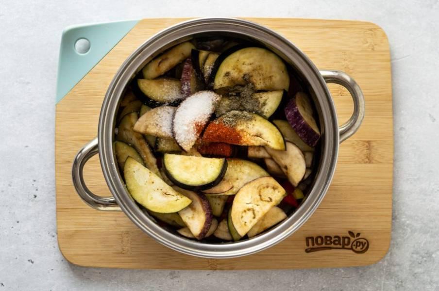 Далее добавьте баклажаны, приправьте их сахаром, черным молотым перцем и паприкой. Тушите около 45-50 минут на небольшом огне.