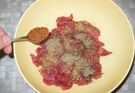 Мясо кладем в удобную миску и добавляем приправ, солим (около 1 чайной ложки), перемешиваем.