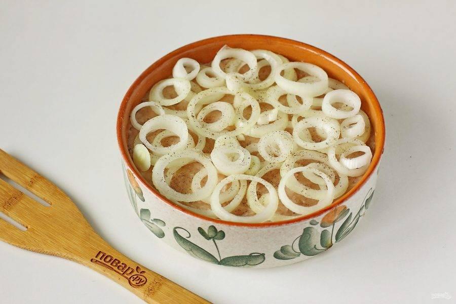 Сверху выложите нарезанный кольцами репчатый лук. Посолите лук и слегка посыпьте молотым перцем.