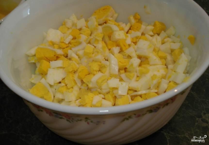 2. Пока курица варится, можно заняться яйцами. 5 штук отварить вкрутую, остудить и порезать мелкими кубиками. Можно также нарезать четвертинками или натереть на терке.