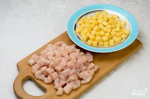 2. Первым делом вымойте и обсушите филе, нарежьте небольшими кубиками и выложите в глубокую мисочку. Туда же отправится и сыр, нарезанный такими же кубиками.