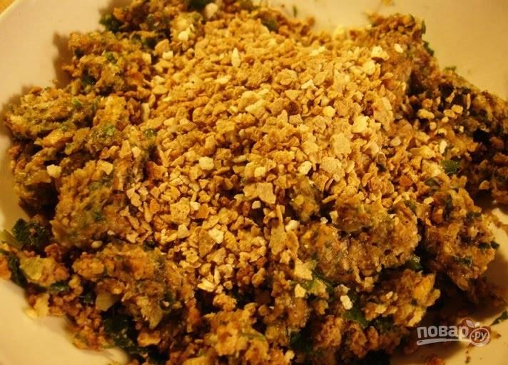 1.Очистите и измельчите лук, чеснок, петрушку, чили. В сковороде растопите сливочное масло и выложите фарш, обжаривайте 10 минут, затем влейте воду, добавьте овощи, зелень. Готовьте все 20 минут под закрытой крышкой, затем снимите крышку и готовьте еще 10 минут. Переложите содержимое сковороды в тарелку, добавьте 3 ложки панировочных сухарей и взбитое яйцо, а также все специи, перемешайте.