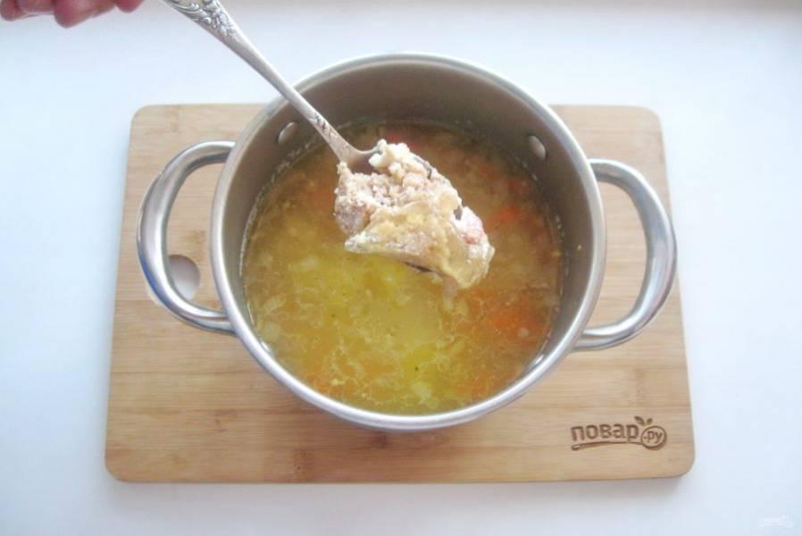 Суп посолите, поперчите и выложите в кастрюлю тушенку.