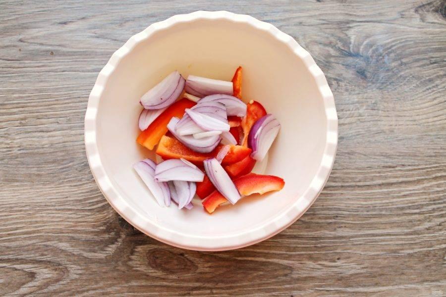 Красный лук почистите и разрежьте вдоль на 6-8 частей. Добавьте его в миску с перцем.