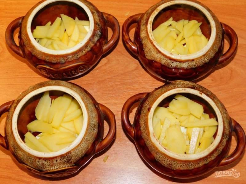 Пока грибы жарятся, в горшочки выложите немного сливочного масла. Сверху нарежьте картофель.