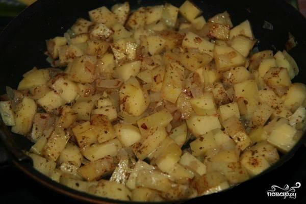 Сначала приготовьте картофельную начинку для пирога. Для этого очистите и нарежьте картофель небольшими кубиками. Лук очистите и нарежьте мелко. Разогрейте сковороду, налейте туда две столовые ложки растительного масла. Обжаривайте картофель с луком в течение 10 минут.