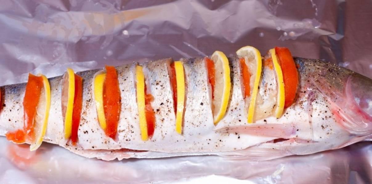 В разрезы вставьте лимонные дольки и помидорки.