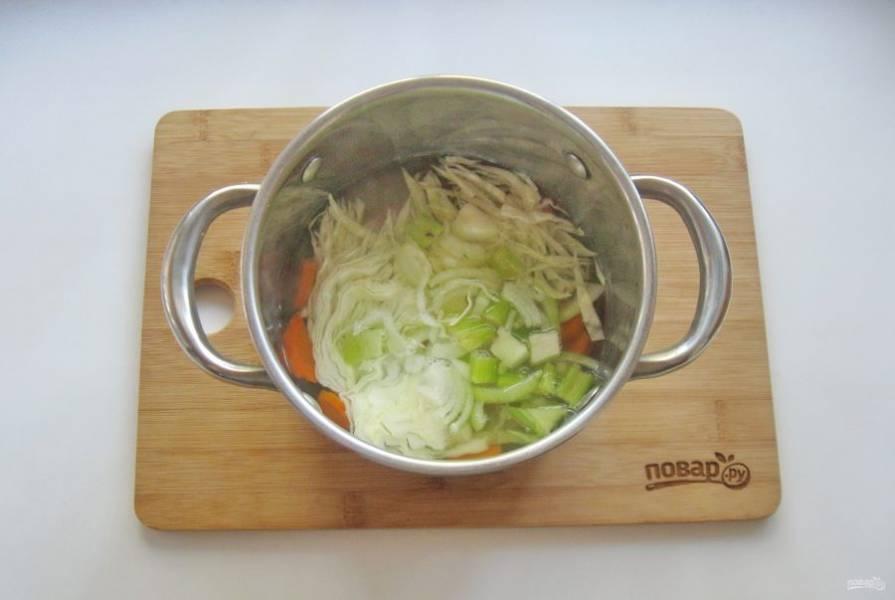 4. Затем выложите в суп капусту, сельдерей, лук. Огонь немного уменьшите и продолжайте варить овощи еще 10 минут.