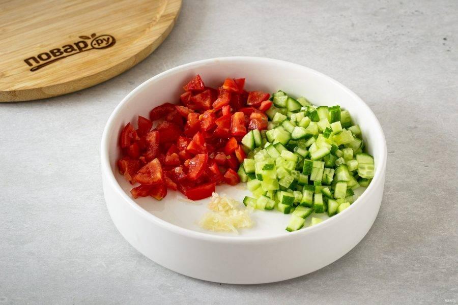 Огурец и помидоры нарежьте на мелкие кубики. Чеснок очистите и пропустите через пресс.