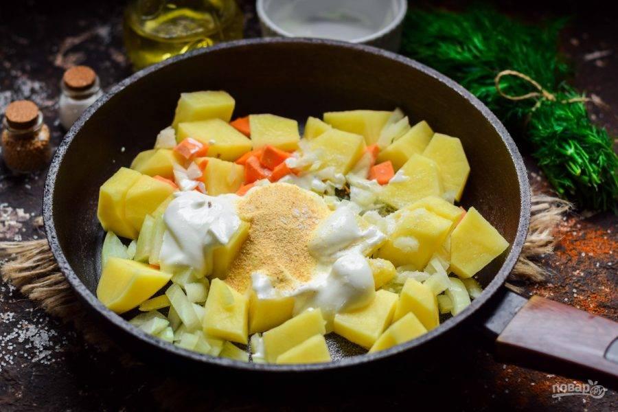 Переложите все ингредиенты в сковороду. Добавьте сметану, чеснок, соль и молотый перец. Влейте 100 мл. воды и тушите картошку под крышкой 25 минут.