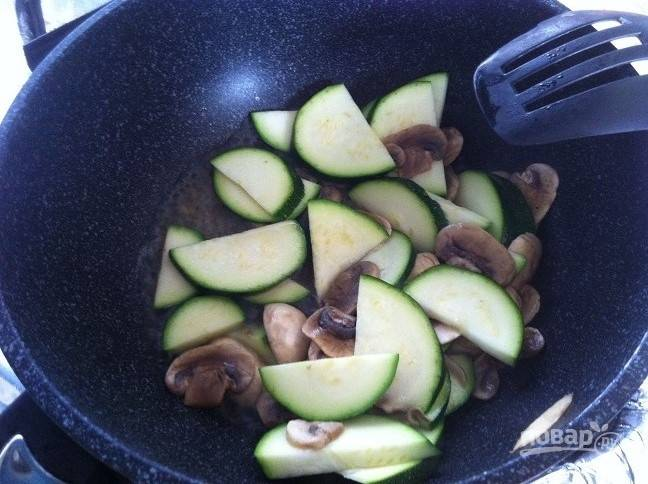 2. Затем добавьте цуккини половинками кружков. Влейте 50 мл воды. Тушите овощи до готовности. В это же время отварите лапшу в подсоленной воде.