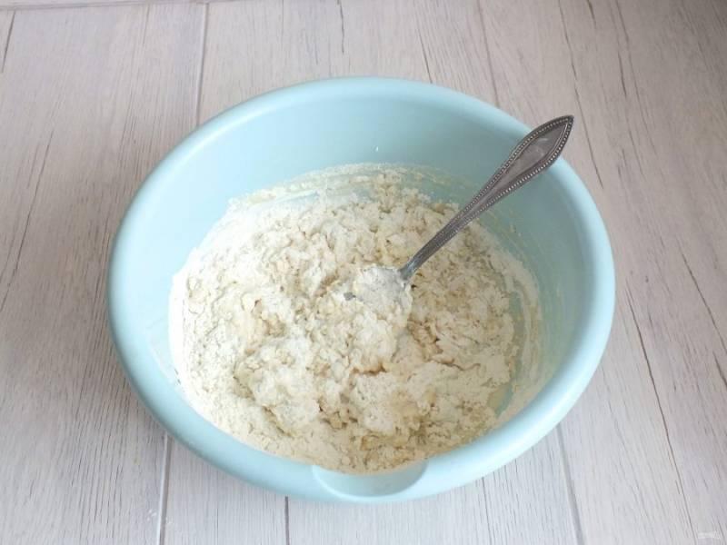 Начните замешивать тесто ложкой. Влейте масло и замешивайте руками.