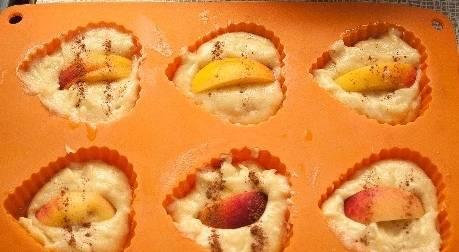 2. Тесто раскладываем по формочкам, в центр каждой помещаем по кусочку персика. Запекаем 20-25 минут при 200 градусах.