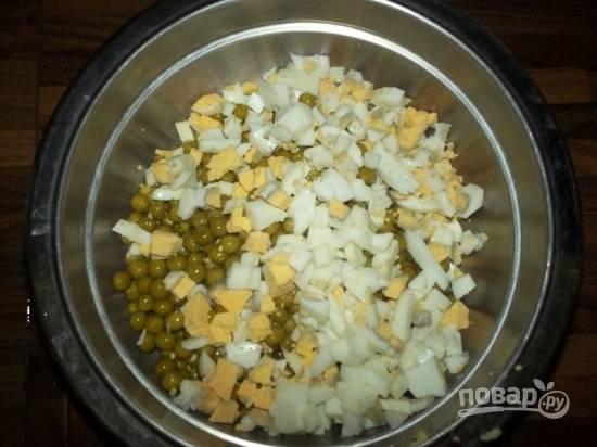 Сваренные вкрутую яйца очистим и нарежем небольшими кубиками. Добавим к горошку и кукурузе.