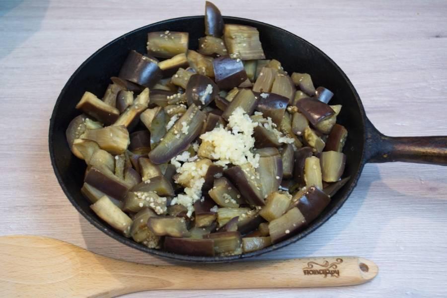 Разогрейте на сковороде 2-3 ст. ложки растительного масла. Поместите в сковороду баклажаны. Выдавите 4-5 зубчиков чеснока через пресс. Обжарьте баклажаны с чесноком, помешивая, на среднем огне (около 30 минут).