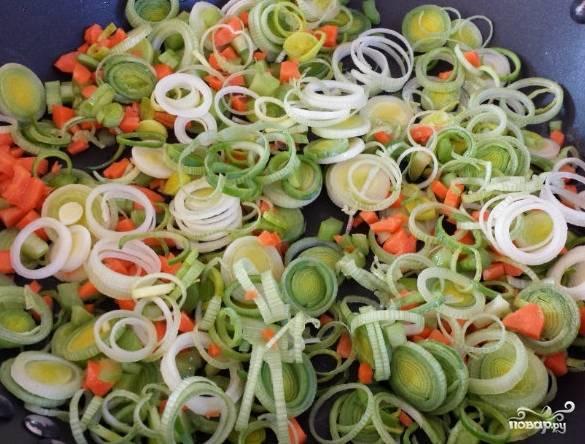 1. В большой сковороде или в сотейнике обжарим измельченный лук-порей, морковь, сельдерей, лавровый лист и измельченный чеснок. Отдельно кипятком заливаем замороженные грибы, чтобы разморозились быстрее.