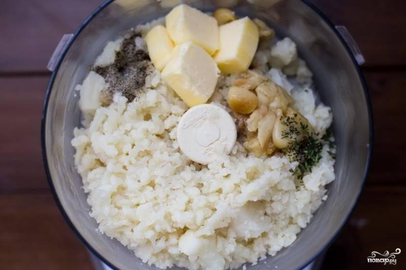 Положите в блендер варёную цветную капусту, чеснок, сливочное масло, специи.