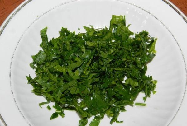 9. Вымыть, обсушить и измельчить зелень. В рецепт приготовления жареных баклажанов с морковью и чесноком можно использовать петрушку, базилик, укроп, кинзу и любую другую зелень по вкусу.
