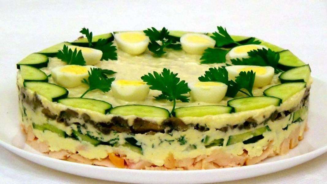 5. Снимите форму, аккуратно прокрутив ее снизу-вверх. Украсьте салат нарезанными огурцами, отварными яйцами и зеленью. Приятного аппетита!