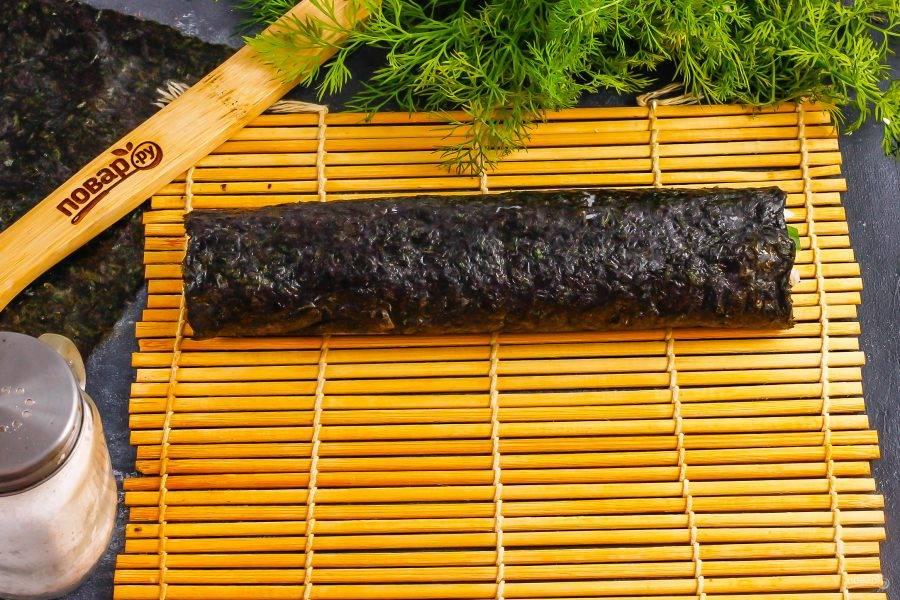 Незаполненный край водорослей смажьте водой. Аккуратно скрутите ролл с помощью коврика.
