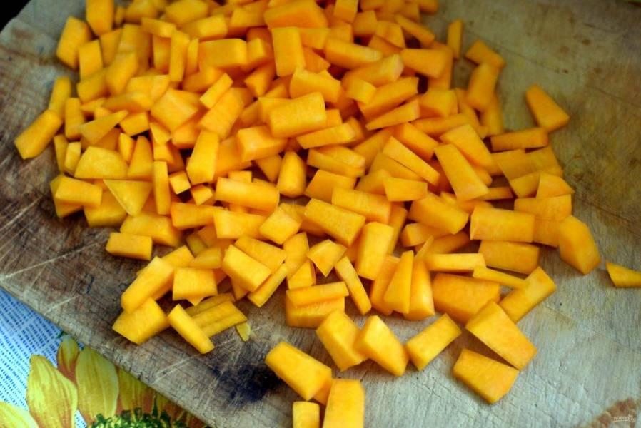 Добавьте к грибам нарезанную некрупными кубиками тыкву и слегка обжарьте ее.