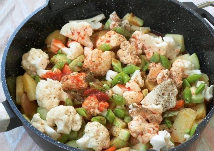 Теперь черед соцветий капусты и стручкового зеленого горошка. Добавьте их на сковороду, залейте разведенной в воде томатной пастой, накройте крышкой и тушите в течение 15 минут. Готовое рагу посыпьте измельченным чесноком и укропом.