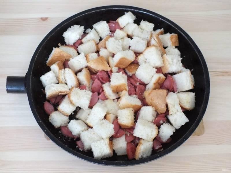 Нарежьте батон средним кубиком и добавьте к сосискам. Обжаривайте 2-3 минуты, чтобы хлеб подрумянивался, помешивайте.