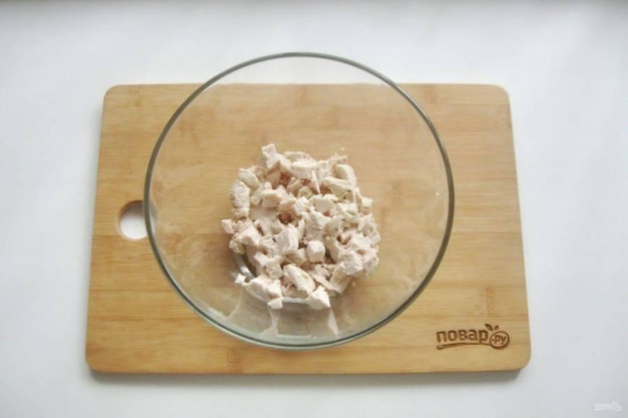 Нарежьте курицу небольшими кубиками и выложите в салатник.