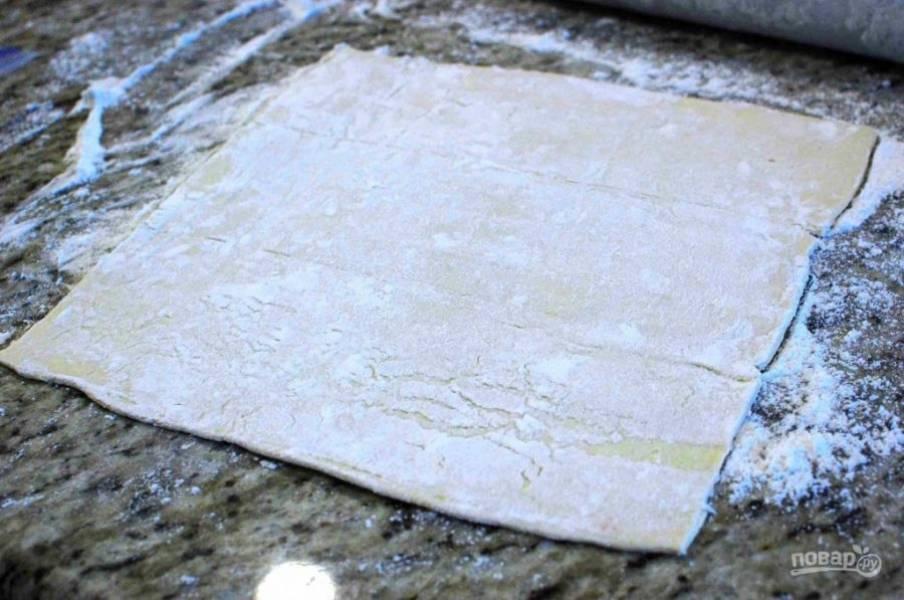 3.Заранее разморозьте тесто при комнатной температуре. Посыпьте ровную поверхность мукой, раскатайте на нем один лист размороженного теста в квадрат.