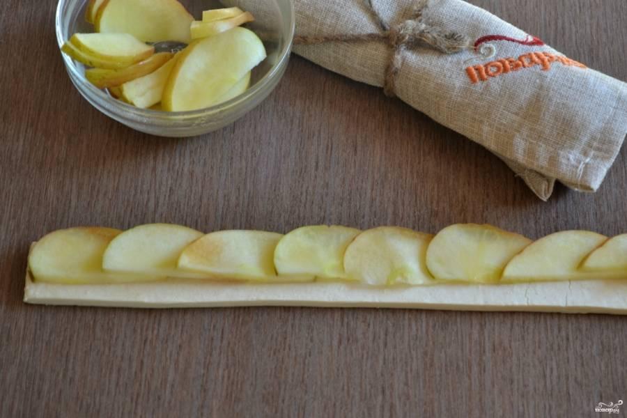 Слоеное тесто порежьте на полоски шириной 3 см. Выложите яблочные дольки на тесто, как показано на фото.
