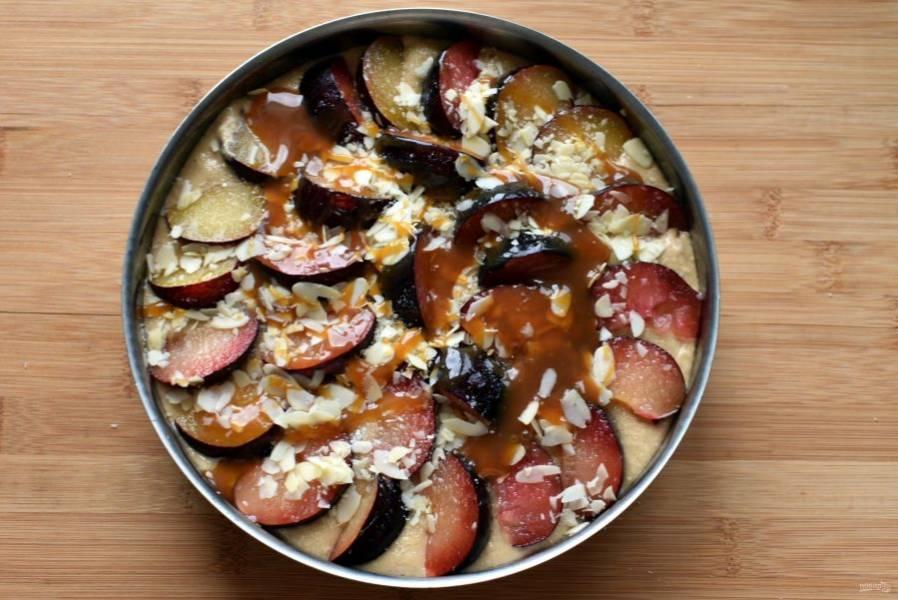 Выложите сливу на пирог, посыпьте сверху немного сахаром, затем миндальными лепестками и немного карамелью.