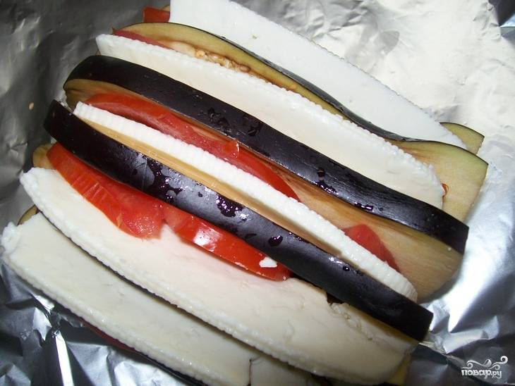 В каждый разрез баклажана вложить по паре кружочков помидора и ломтику брынзы.  Уложить баклажан на фольгу, полить ароматизированным маслом и завернуть.