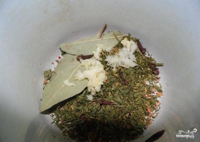 В отдельной посуде (к примеру — в эмалированой маленькой кастрюльке) приготовьте настой из трав. Для этого все специи тщательно измельчите пестиком, чеснок пропустите через пресс. Положите все ингредиенты в кастрюльку, залейте кипятком. Накройте крышкой и дайте постоять пять минут.
