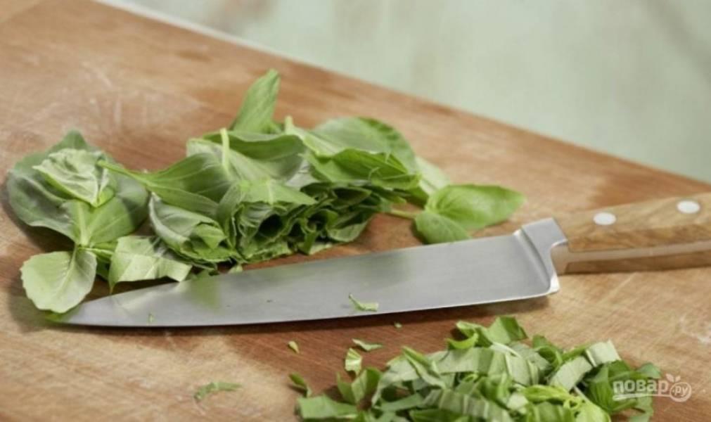 Вымойте зелень базилика. Отделите зеленые листики от черешков и мелко нарубите их при помощи острого ножа.