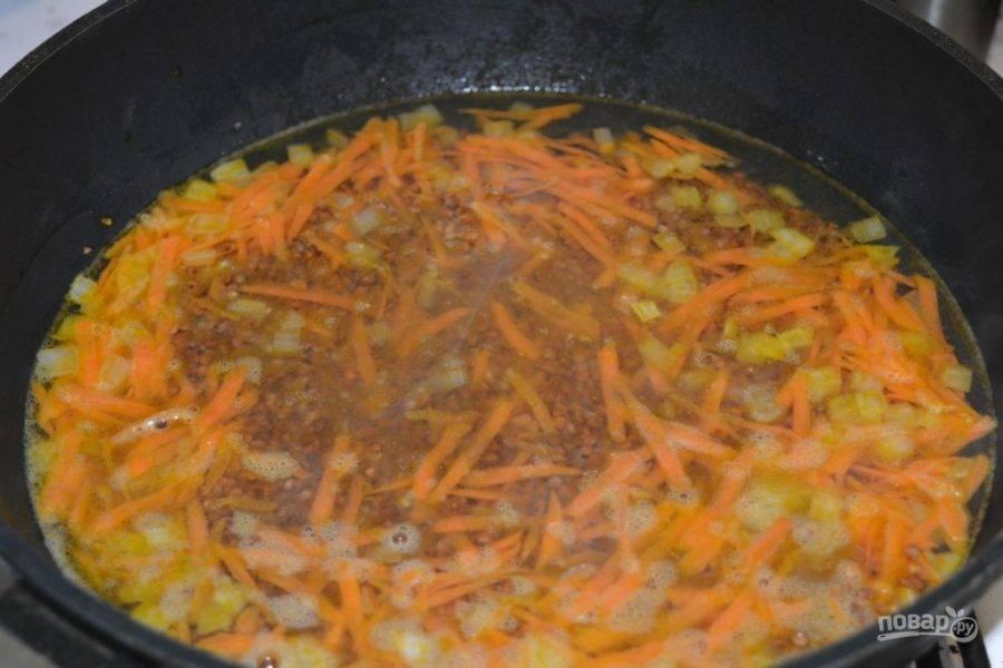 Когда овощи подрумянятся, всыпьте к ним крупу и аккуратно разровняйте по всей сковороде. Залейте водой или бульоном на два пальца выше гречки и поставьте тушить.