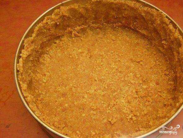 1.Печенье измельчаем в крошку, масло растапливаем и вливаем к печенью, все перемешиваем. В форму для выпекания застилаем пергамент, затем песочное тесто выкладываем в форму.