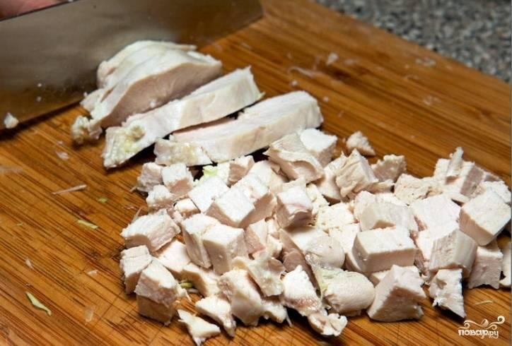 Отварим до готовности куриное филе, остудим и нарежем кубиками.